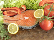 Raw salmon steak on a wooden board surrounded by vegetables and spices. Royalty Free Stock Photo