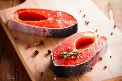 Raw salmon steak on wooden cutting board Stock Image