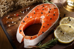 Raw salmon steak on wooden cutting board. With herbs Stock Photography
