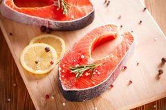 Raw salmon steak on wooden cutting board. With herbs Royalty Free Stock Photos