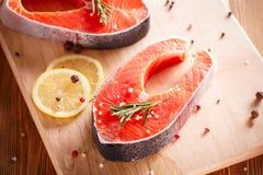 Raw salmon steak on wooden cutting board Royalty Free Stock Photos