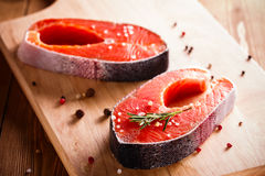 Raw salmon steak on wooden cutting board. With herbs Royalty Free Stock Image