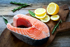 Raw salmon steak on wooden cutting board with herbs and lemon Stock Photos