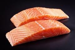 Raw Salmon Steaks. Two raw salmon steaks on black background Royalty Free Stock Photos
