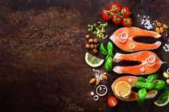Raw salmon steaks, aromatic herbs, onion, lemon, salt and fresh vegetables for cooking on wooden background. Copyspace royalty free stock photo
