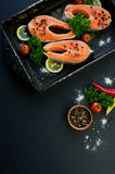 Raw salmon steaks on a dark background Royalty Free Stock Images