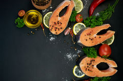 Raw salmon steaks on a dark background Royalty Free Stock Photography