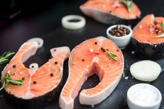 Raw salmon steaks on the dark stone background. Fresh salmon steaks with ingredients for cooking on a wooden board, top view Royalty Free Stock Photography