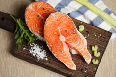 Raw salmon steaks. Fresh salmon steaks on a wooden cutting board, close up Royalty Free Stock Photo