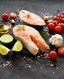 Raw salmon steaks. And ingredients on a black slate board royalty free stock images