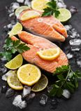 Raw salmon steaks. And ingredients on a black slate board stock photo