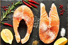 Raw salmon steaks. And ingredients on slate background Royalty Free Stock Image