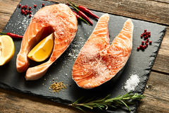 Raw salmon steaks. And ingredients on slate background Stock Images