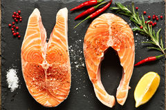 Raw salmon steaks. And ingredients on slate background Stock Photo