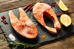 Raw salmon steaks. And ingredients on slate background Royalty Free Stock Photos