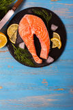 Raw salmon steaks and ingredients on slate background. Stock Photos