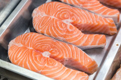 Raw salmon steaks on metal plate in shop-window. Raw salmon steaks on metal box in shop-window Stock Photography