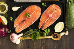 Raw salmon steaks over wooden background. Raw salmon steaks wigh vegetables ready for grilling Royalty Free Stock Images