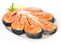 Raw salmon steaks on a plate. Plate with many raw salmon steaks on white background Royalty Free Stock Image