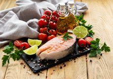 Raw salmon steaks. And ingredients on a old wooden table stock photography