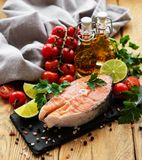 Raw salmon steaks. And ingredients on a old wooden table royalty free stock images