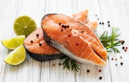 Raw salmon steaks. And ingredients on a old wooden table royalty free stock photo