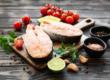 Raw salmon steaks. And ingredients on a old wooden table royalty free stock image