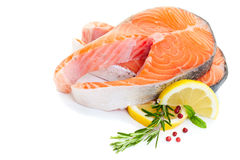 Raw Salmon Steaks. Salmon steak decorated with basil, lemon and rosemary on a white background Stock Image