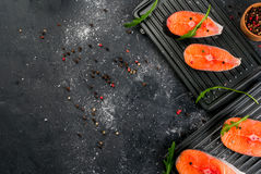Raw salmon steaks. Raw uncooked salmon steaks on the boards for the grill, on a dark gray stone kitchen table. With salt, spices, seasonings, herbs and Royalty Free Stock Photos