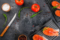 Raw salmon steaks. Raw uncooked salmon steaks on the boards for the grill, on a dark gray stone kitchen table. With salt, spices, seasonings, herbs and Royalty Free Stock Images