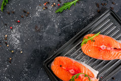Raw salmon steaks. Raw uncooked salmon steaks on the boards for the grill, on a dark gray stone kitchen table. With salt, spices, seasonings, herbs and Stock Image