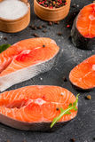 Raw salmon steaks. Raw uncooked salmon steaks on a dark gray stone kitchen table. With salt, spices, seasonings, herbs and vegetables for cooking.  Close view Royalty Free Stock Photos