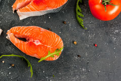 Raw salmon steaks. Raw uncooked salmon steaks on a dark gray stone kitchen table. With salt, spices, seasonings, herbs and vegetables for cooking. Close top view Stock Images