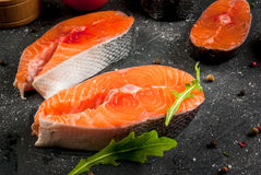 Raw salmon steaks. Raw uncooked salmon steaks on a dark gray stone kitchen table. With salt, spices, seasonings, herbs and vegetables for cooking. Close view Stock Photo