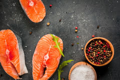 Raw salmon steaks. Raw uncooked salmon steaks on a dark gray stone kitchen table. With salt, spices, seasonings, herbs and vegetables for cooking.  Top view Royalty Free Stock Photography