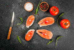 Raw salmon steaks. Raw uncooked salmon steaks on a dark gray stone kitchen table. With salt, spices, seasonings, herbs and vegetables for cooking. Top view, copy Stock Images