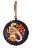 Raw salmon steaks with vegetables in the iron pan.  Royalty Free Stock Image