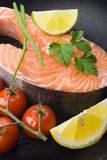 Raw salmon steaks with vegetables in the iron pan.  Royalty Free Stock Photo