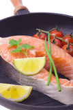 Raw salmon steaks with vegetables in the iron pan.  Stock Images