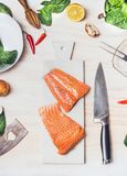 Raw salmon steaks on white cutting board with knife on kitchen table background with ingredients, top view. Healthy eating and coo Royalty Free Stock Photos