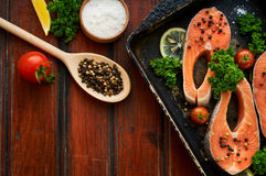 Raw salmon steaks on a wooden background Stock Photography