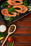 Raw salmon steaks on a wooden background Royalty Free Stock Image