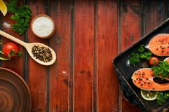 Raw salmon steaks on a wooden background Royalty Free Stock Images