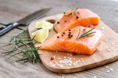 Raw salmon steaks on the wooden board. Close up Stock Images