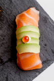 Raw Salmon Sushi Topping with Avocado and Ikura Salmon Roe Served on Black Stone Plate. Royalty Free Stock Photo