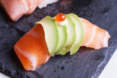 Raw Salmon Sushi Topping with Avocado and Ikura Salmon Roe Served on Black Stone Plate. Royalty Free Stock Images