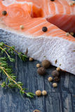 Raw salmon with thyme and pepper on a wooden board. close-up Royalty Free Stock Photo