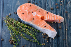 Raw salmon with thyme and pepper on a wooden board. close-up Stock Photo