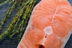 Raw salmon with thyme on a wooden board. close-up Stock Image