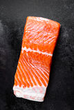 Raw salmon or trout sea fish fillet on black metal background, top view Stock Photos